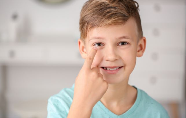 Boy putting in contact lens as one way to stop progression of myopia in his eye